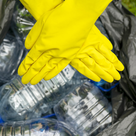Crossed hands in yellow gloves against a black pklastic bag with empty plastic bottles. Plastic ban.