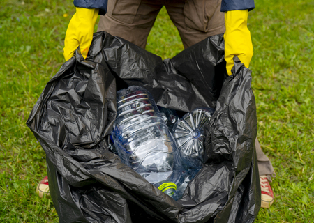 Man holding black plastic trash bag with empty plastic bottles. Grass background. Imagens