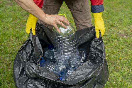 Men collecting trash. Hand putting a plastic bottle in a plastic trash bag.