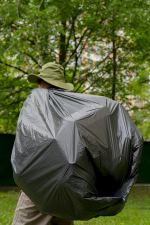 Garbage collection. Man carries a big black trash bag.