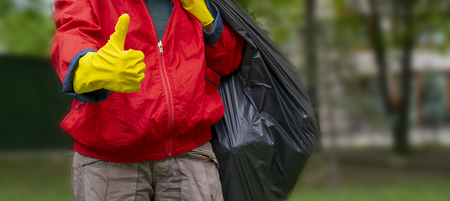 Garbage collection. Man in red coat and yellow gloves showing thumb up, carries a big black bag with trash.