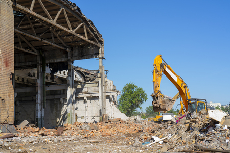 Destruction of the old building. Yellow excavator on the ruins. Imagens