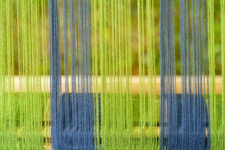 Blue and green threads in an old wooden machine. Standard-Bild - 124966760