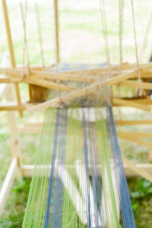 Blue and green threads in an old wooden machine. Standard-Bild - 124964100