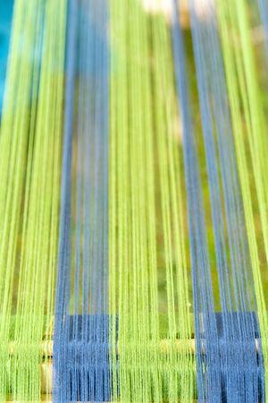 Blue and green threads in an old wooden machine. Standard-Bild - 124964107
