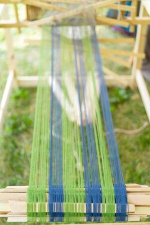 Blue and green threads in an old wooden machine. Standard-Bild - 124964001