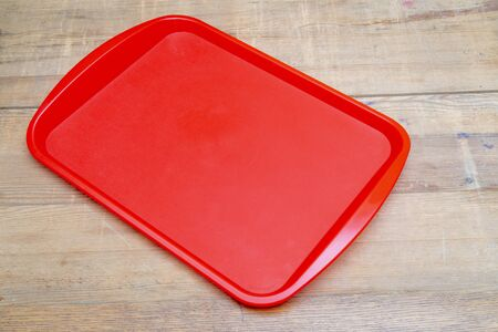 Red plastic dining tray on the table.