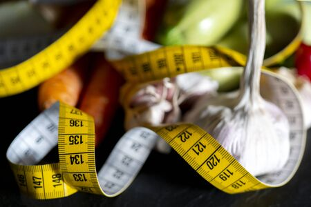 Measuring tape for measuring the circumference. Vegetables for diet cooking. Banco de Imagens - 124964017