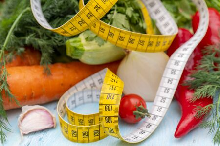 Measuring tape for measuring the circumference. Vegetables for diet cooking. Banco de Imagens - 124963678