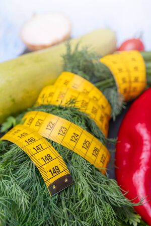 Measuring tape for measuring the circumference. Vegetables for diet cooking. Banco de Imagens - 124963690