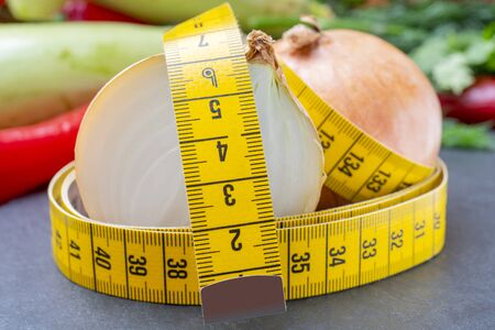 Measuring tape for measuring the circumference. Vegetables for diet cooking. Banco de Imagens - 124963695