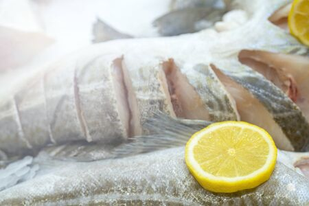 Frozen fish and yellow lemon on ice. Stock Photo