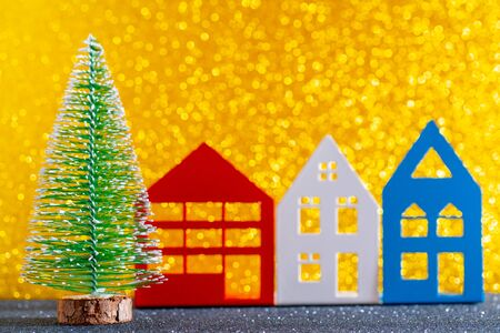Green christmas tree on shiny background. Beautiful bokeh. Small houses.