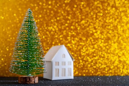 Green christmas tree on shiny background. Beautiful bokeh. Little white house.