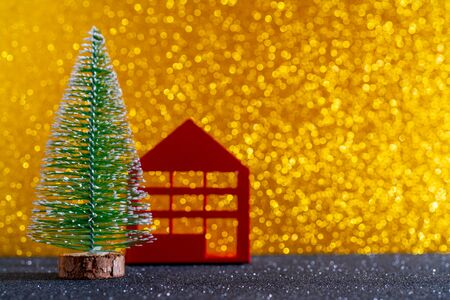 Green christmas tree on shiny background. Beautiful bokeh. Little red house.
