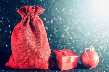 Fondo negro brillante de Navidad. Bolsa de regalo roja y juguetes navideños.