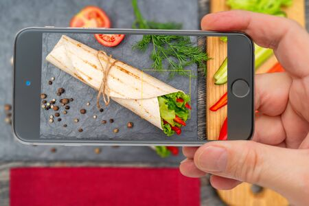 Vegetable roll for healthy lifestyle. Photo smartphone. Smartphone in hand. Roll on screen.