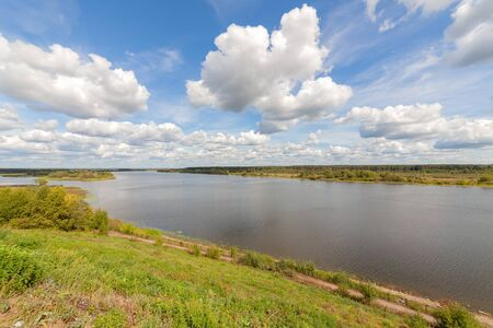 Wide river. Summer sunny day. White clouds on a blue sky. Banco de Imagens
