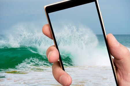 Surf waves on smartphone screen. Clear sea water. Stormy sea. 스톡 콘텐츠