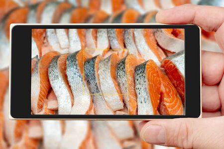 Steaks of fresh salmon on smartphone screen. Selling on ice. Seafood shop.