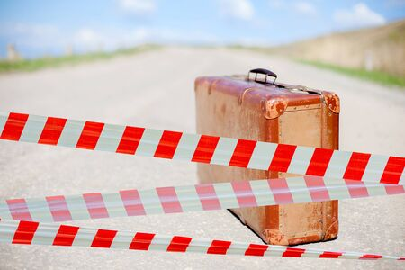 Restrictive tape. Traveler and brown suitcase on deserted road. Summer for travel. Time to rest.