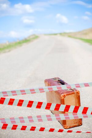 Restrictive tape. Traveler and brown suitcase on deserted road. Summer for travel. Time to rest.  Stock Photo