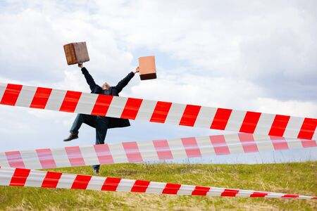 Restrictive tape. Traveler with suitcases. Summer for travel. Man goes on vacation. Stock Photo
