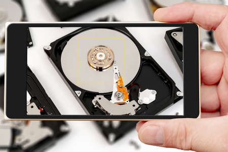 Computer hard drive on smartphone screen. Repair of electronic devices. Data store.