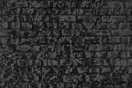 The background of the old black brick wall for design interior and various scenes or as a background for video interviews.