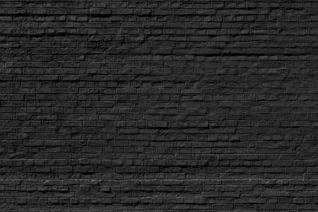 The background of the old black brick wall for design interior and various scenes or as a background for video interviews. Stockfoto
