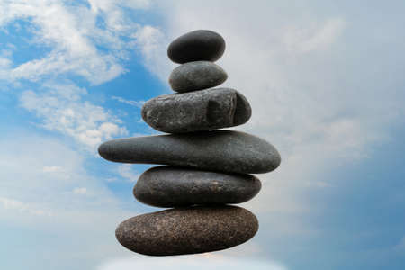 Stack of pebbles in an unstable state. A pyramid made of flat stones.