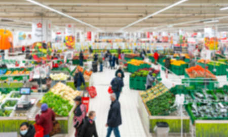 Blurred supermarket. Selling vegetables and fruits in a retail store. Blurred background of customers in medical masks in a store.
