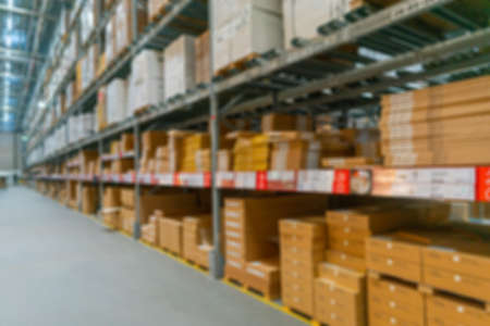 Blurred background of the warehouse. Boxes with goods on the shelves. Archivio Fotografico