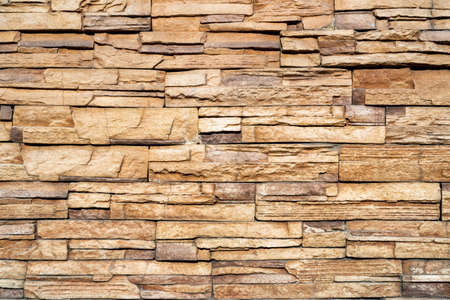 Wall of yellow stone. Abstract natural background. Uneven stone surface.