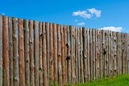 Log wooden fence. The texture of the old wooden fence. Wooden vintage background.