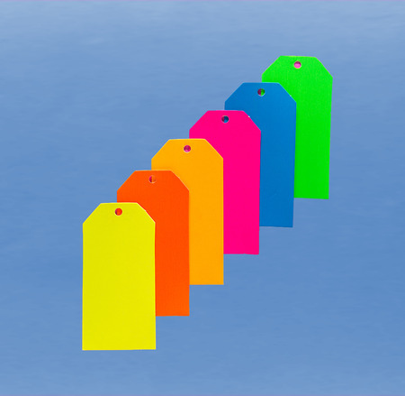 Six Colorful Paperboard Tags On Top of Blue Background