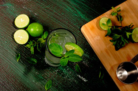 Mojito, cocktail of Cuban origin on a green table decorated with cocktail elements. Wooden background.