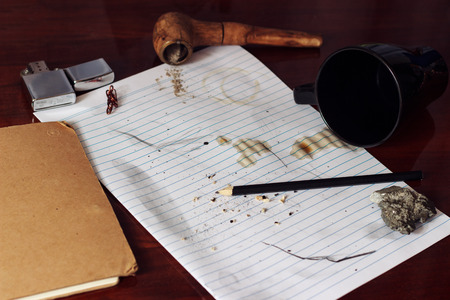 ard: Spilled coffee on paper with pipe, lighter, pencil, paper and coffee cup