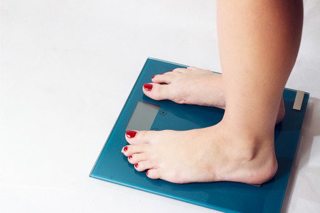Body part - woman legs on scaleweight
