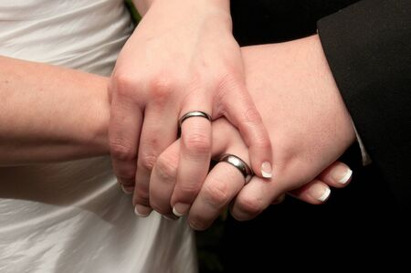 Bride and groom holding hands while displaying their wedding rings. Stock Photo - 8709265