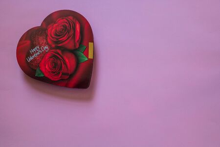 An unopened red heart shaped box with roses on it of Valentine chocolates inside on an angle with a pink background for copy space Banco de Imagens