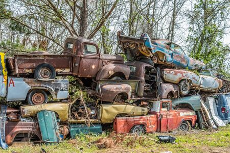 Wall of old vintage cars trucks and other junk piled up high just weathering away Reklamní fotografie