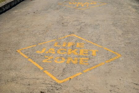 On the boat ramp in the park at the river is two signage painted on the cement to wear a life jacket zone before entering the water