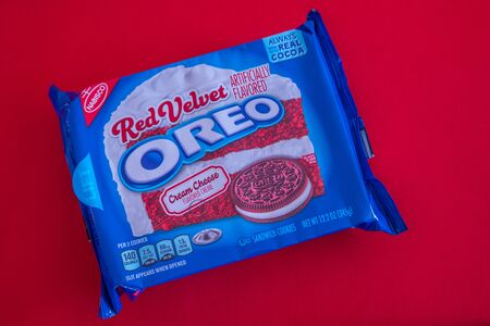 A package of red velvet Oreo cookies for Valentine's day unopened on a red background closeup on an angle