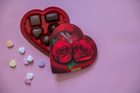 An opened heart shaped box of assorted chocolates with candy hearts alongside with Valentine sayings on a pink background closeup copy space