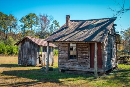 A small abandoned homestead with a shed and bicycle next to it in the north Georgia mountains still standing weathered and decaying on a sunny day in autumn