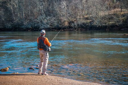 A man fishing at the boat ramp at the Chattahoochee river wearing a fishing vest waiting for a catch on a sunny day in winter