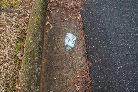 A discarded beverage can wrapped in a plastic bag tossed into the street along the curb of the road polluting the environment from carelessness Stock Photo
