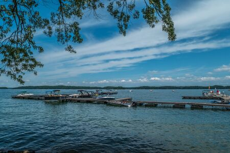 Boats moored at the docks with lots of water sport activity on the lake on a bright warm sunny day in summertime