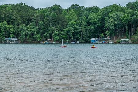 A couple in kayaks fishing on the lake on a cloudy day in summer with docks boats and the woodlands in the background